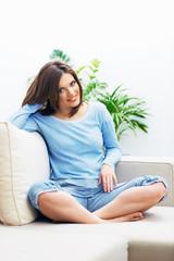 Smiling woman sitting on sofa.