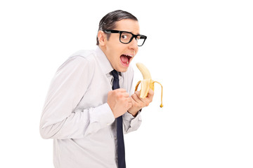 Scared man with glasses eating a banana