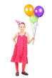 Little girl holding a bunch of balloons