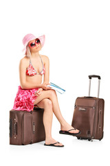 Female tourist holding a ticket and sitting on her luggage