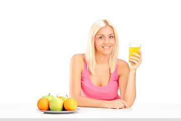 Blond woman drinking an orange juice seated at table