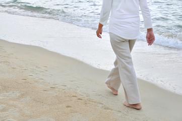 Woman walking alone on the sandy beach