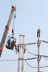 Electrician working at height by connect a high voltage wire.