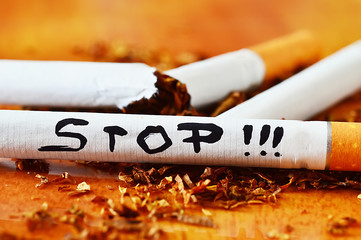 cigarettes with a brown filter close up and stop message text