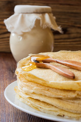 Russian pancakes with wooden spoons, honey and clay jug
