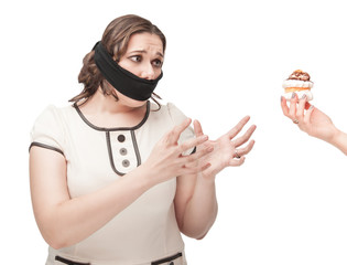 Plus size woman gagged stretching hands to pastry