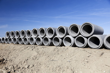 Row of concrete pipes. Blue sky.