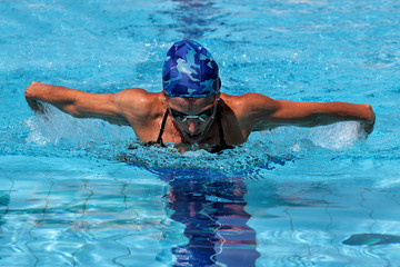 Woman swimming in butterfly style in pool