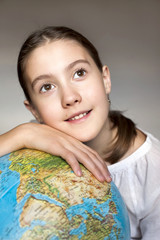 Thoughtful girl with blue round globe dreaming about adventure.