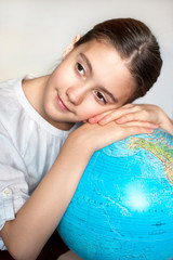 Dreaming about holidays. Thoughtful smiling girl with blue globe