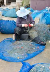 fisherman take fish out of a net