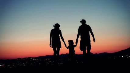 Family walking at sunset.  Silhouette of family.