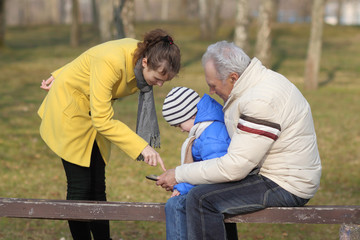 Grandfather and grandson are looking tablet on bench outdoors