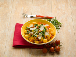 gnocchi with arugula tomato and parmesan cheese