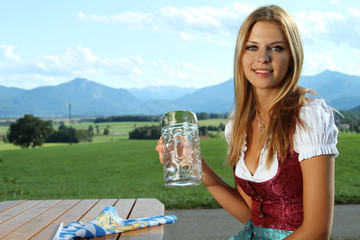 Frau im Dirndl mit Bier auf dem Land