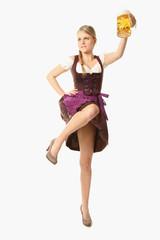 Frau im Dirndl mit Bier springt in die Luft