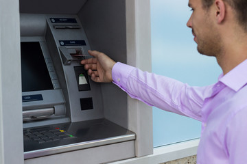 Man takes a credit card from an ATM