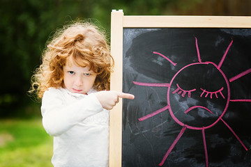 Little girl dissatisfied points on the board with a picture. Sad