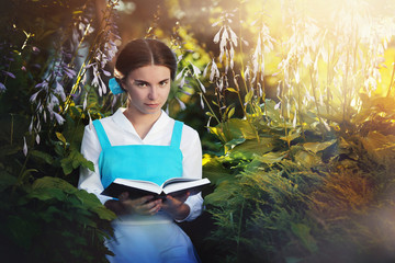 beautiful girl in cosplay Belle reading a book sitting on the gr