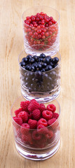 Black, red currants and raspberries in glasses