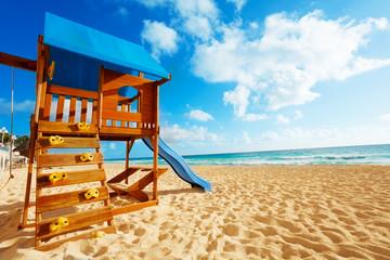 Playground house on the sand beach near sea