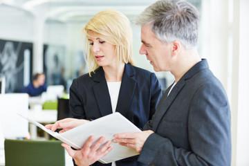 Zwei Geschäftsleute mit Akte reden im Büro