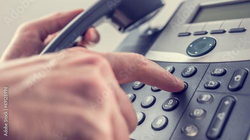 Leinwanddruck Bild Man dialling out on a landline telephone