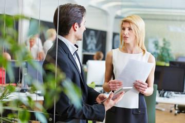 Geschäftsfrau und Geschäftsmann reden im Büro