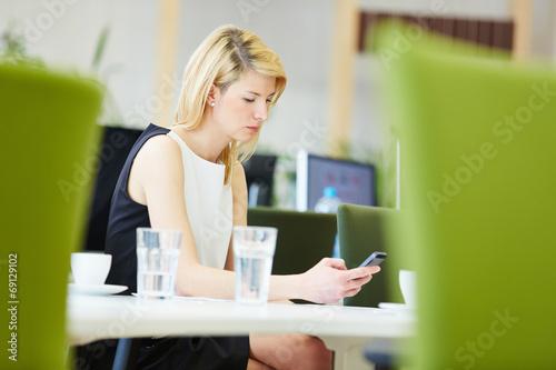 canvas print picture Geschäftsfrau im Büro schaut auf Smartphone