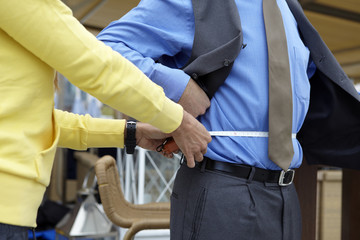 Personal trainer measuring a businessman