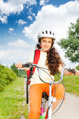 Pretty girl with long hair in helmet rides a bike