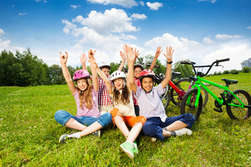 Happy kids in helmets on grass with hands up