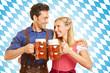 Paar stößt mit Bier an in bayrischer Tracht