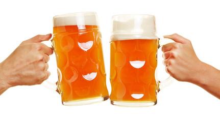 Zwei Hände stoßen mit Bier an