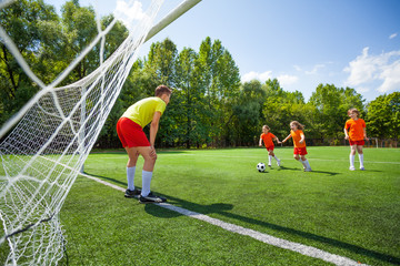 Children play football together, goalkeeper wait