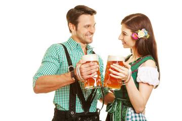 Paar in Tracht prostet sich mit Bier zu