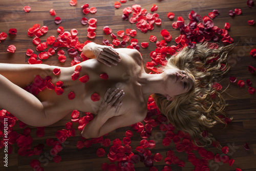 Naga kobieta w płatkach róż