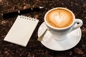 Open a blank white notebook, pen and cup of coffee on marble des