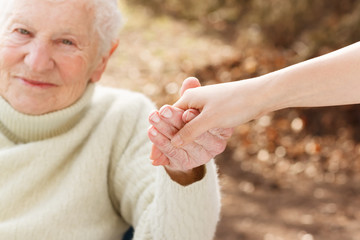 Senior woman holding hands with young lady