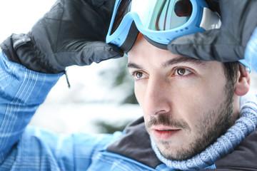 Mann im Skiurlaub mit Skibrille im Winter