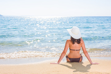 Beautiful back side of model in bikini and hat sitting