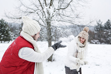 Paar bei Schneeballschlacht im Winter
