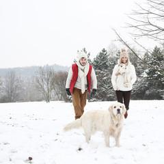 Paar im Winter geht mit Hund spazieren