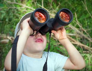 The little boy looks up at binoculars