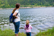 woman with 	daughter looking on a lake