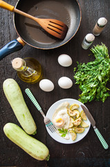 fried eggs and chopped zucchini with parsley on the plate