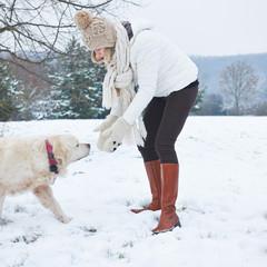 Frau geht mit Hund im Winter Gassi