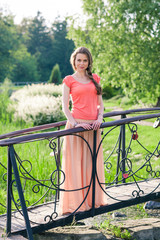 Beautiful woman standing in a park near the bridge
