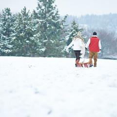 Paar zieht Schlitten auf Berg im Winter