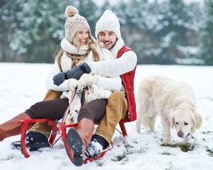 Paar mit Hund beim Rodeln im Winter